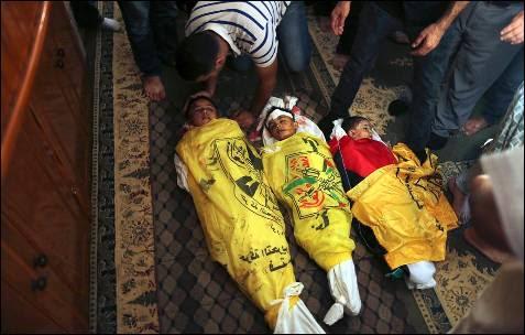 Varias personas se reúnen alrededor de los cuerpos de tres niños palestinos, entre ellos dos hermanos de la familia Alwán, muertos por el disparo de un tanque israelí, durante su funeral en la ciudad de Gaza.