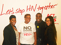 Photo of three women and one man standing in front of Let's Stop HIV Together backdrop.