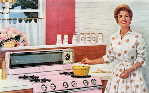 A happy housewife cooks on her new pink range, with a pot on the cooktop and a pumpkin pie in the oven, 1957.