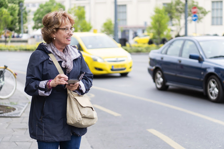Woman with a smartphone and taxi in the background