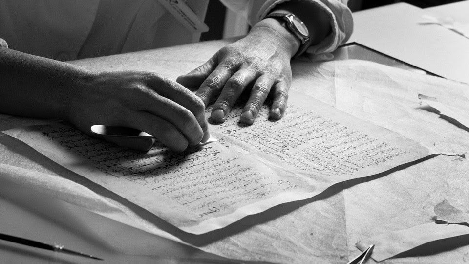 Black-and-white image of a pair of hands on top of a manuscript