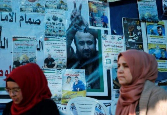 Des palestiniennes passent devant une affiche de Marwan Barghouthi à Ramallah, le 24 avril 2017 - ABBAS MOMANI, AFP