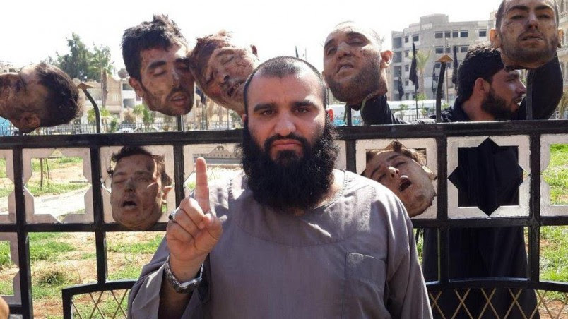 ISIS jihadist                                                 posing with severed                                                 heads in Syria