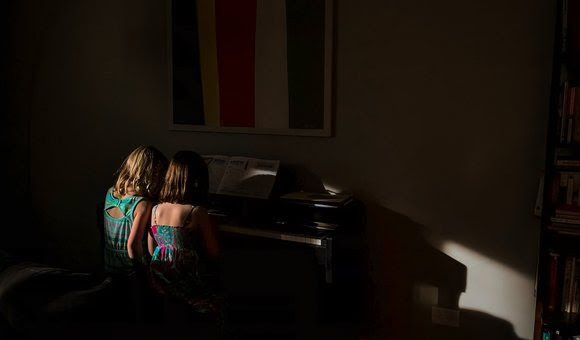 Best friends sit together trying to play the piano.