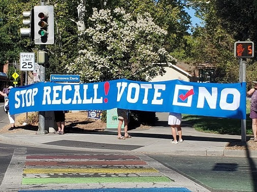 """5 people on a street corner by the Davis Farmer's Market hold a large blue banner with white text reading """"Stop recall! Vote No"""""""