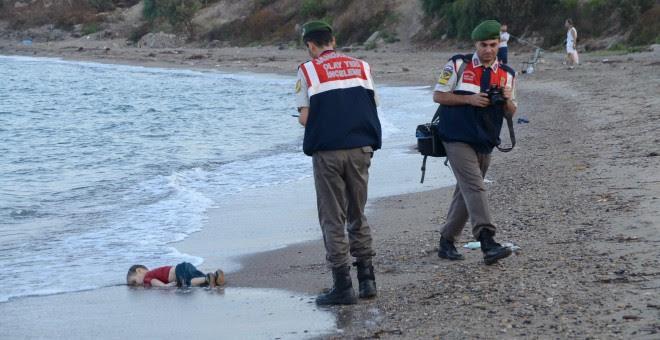Dos agentes de la gendarmería turca, junto al cadaver de un niño que formaba parte del grupo de refugiados sirios que naufragaron intentando llegar a la isla de Kos. REUTERS/Nilufer Demir