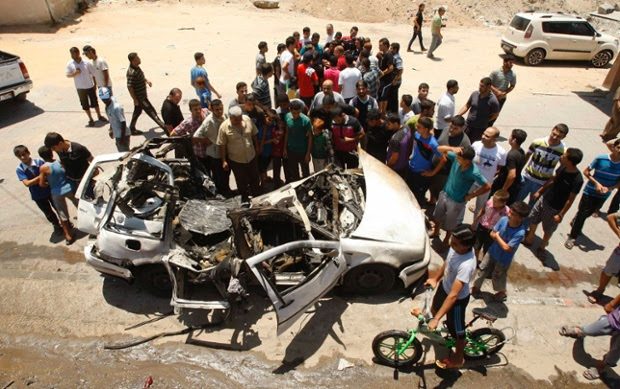 Palestinians gather around the remains of a car which police said was targeted in an Israeli airstrike in the northern Gaza Strip.