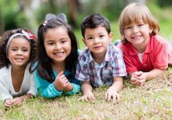 Photo of four smiling children on the grass