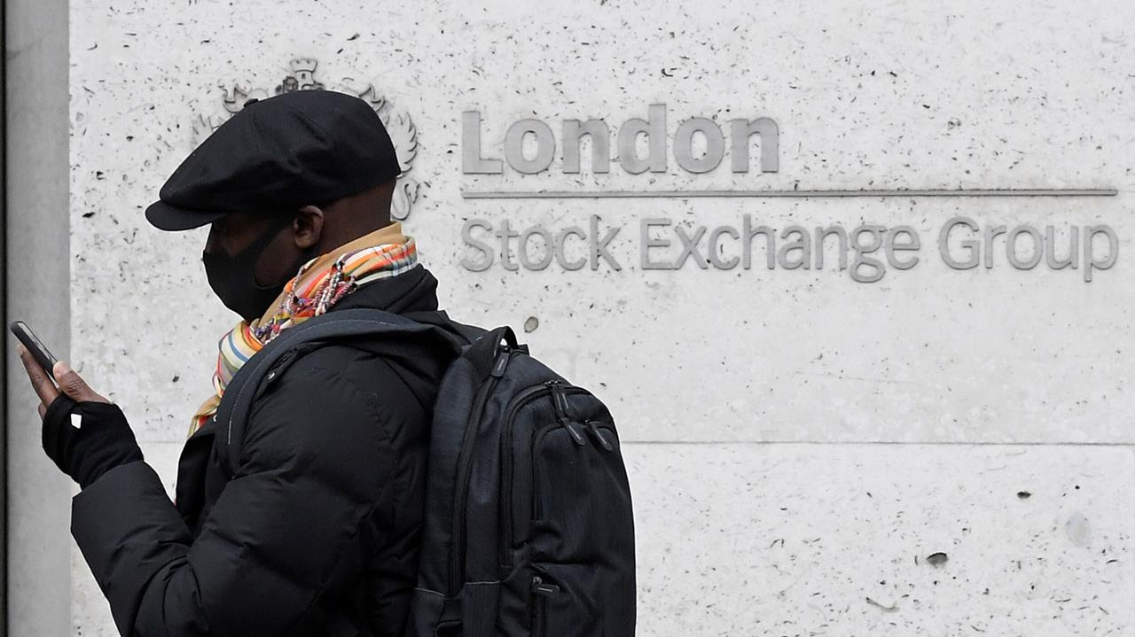A man wearing a protective face mask walks past the London Stock Exchange Group building as investors fear that the coronavirus outbreak could stall the global economy, in London, Britain.