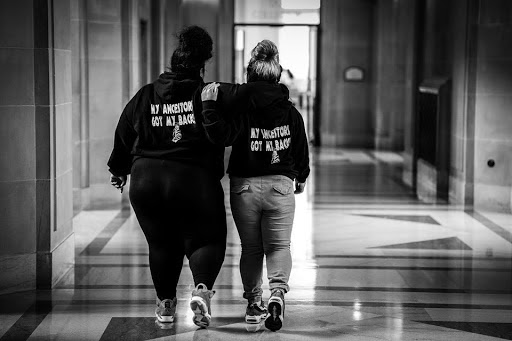 """a black and white photo of two young women walking away with their arms interlocked. Their matching hoodies read: """"my ancestors got my back."""""""