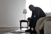 Older male sitting alone on bed