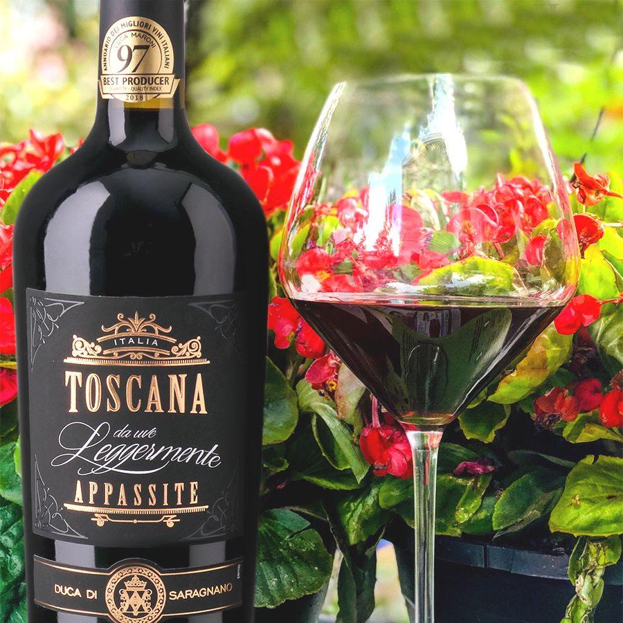 Bottle and glass of Toscana Rosso da Uve Leggermente Appassite set among vibrant red blossoms.