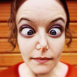 closeup of cross-eyed woman with nostrils pinched shut