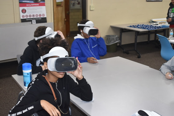 Student sitting at table wearing VR goggles