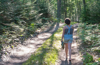 Girl walks on wooded trail at Cheboygan State Park