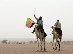 A man holds the flag of the National Movement for the Liberation of Azawad (MLNA) during a demonstration in support of the MLNA on July 28, 2013 in Kidal, northern Mali