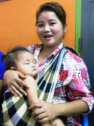 A baby naps in his mother's arms outside the flu vaccination clinic at Vientiane's busy maternal hospital. Laos, 2012.