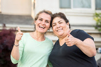 Two women giving the thumbs up