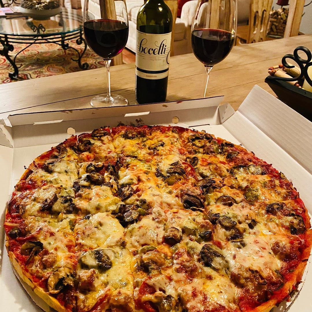 Bottle and glasses of Sangiovese IGT Rosso Toscana by Bocelli 2017 next to sumptuous pizza - ready to eat.