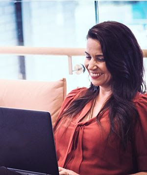 woman sits on a couch using laptop and smiling