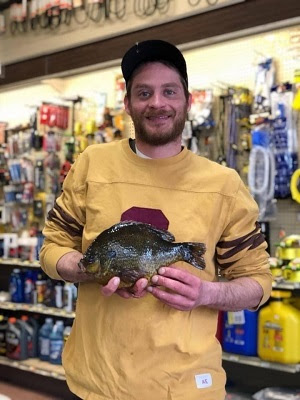 man holding pumpkinseed fish