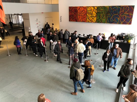 A crowd of people lining up to enter the Museum of Modern Art