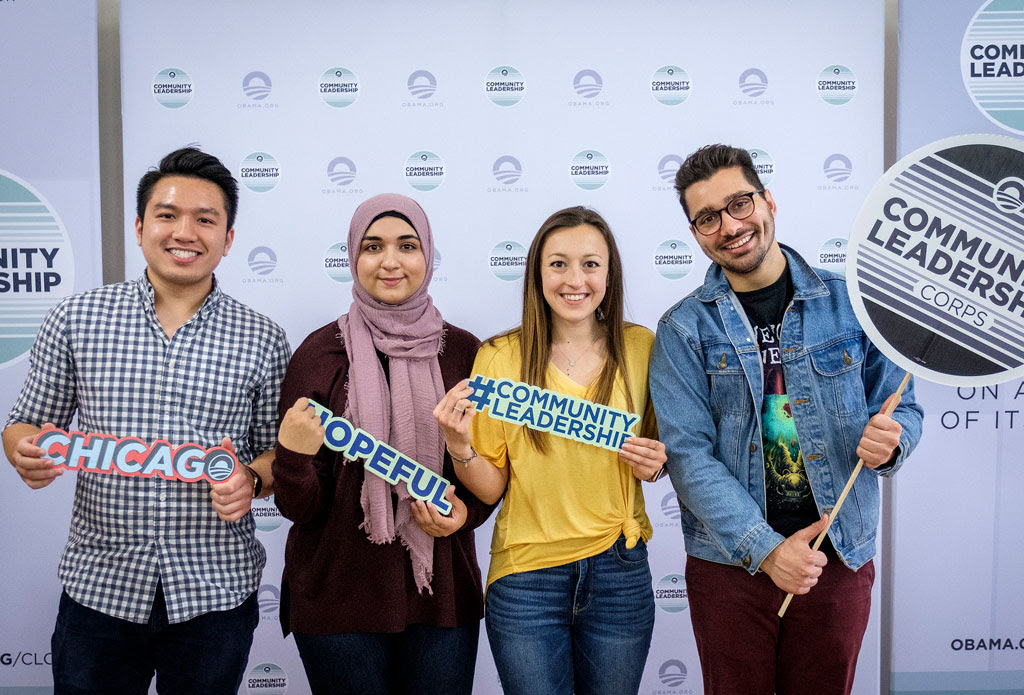 The four young leaders of Info 312 pose with the #CommunityLeadership and other decals.