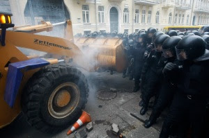People use a tractor while trying to break through police lines near the presidential administration building during a rally held by supporters of EU integration in Kiev
