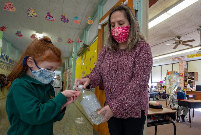 Kindergarten teacher Heather Brandt, of Levittown, squirts hand sanitizer on the hands of Nadia Lentz, 6, of Levittown, before she reenters the classroom at St. Michael the Archangel.