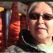 Woman with drying salmon in background