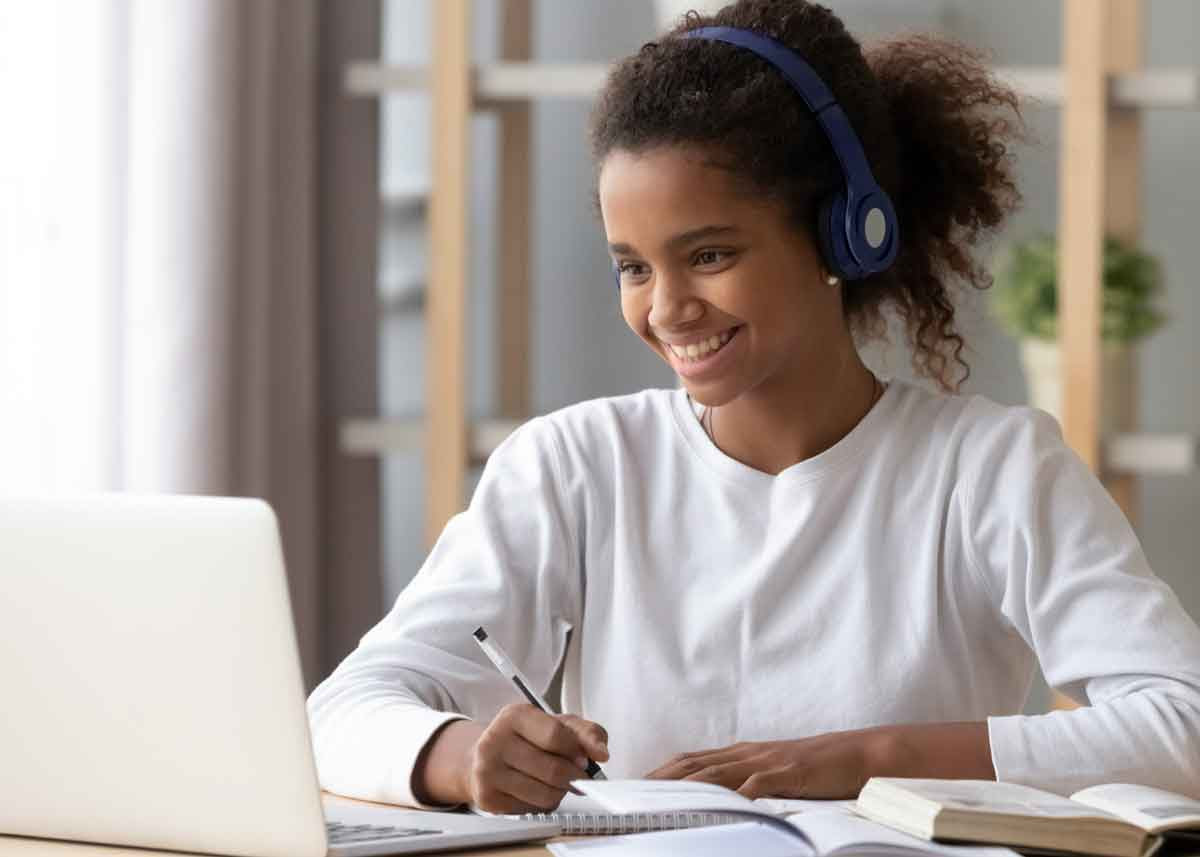 student smiling while looking at a computer