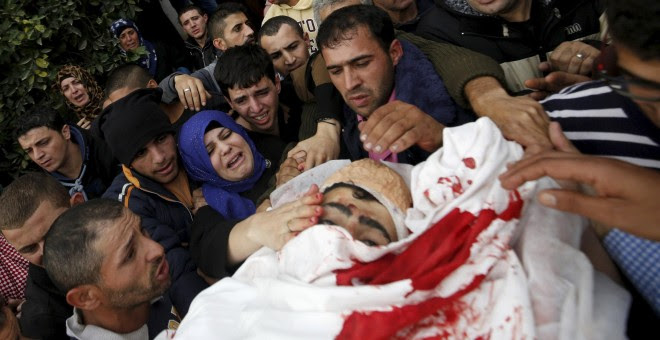 Familiares del joven palestino Yehia Taha, asesinado por las tropas israelíes, según dijeron los médicos, durante disturbios en la aldea cisjordana de Qatnna.- REUTERS/Mohamad Torokman