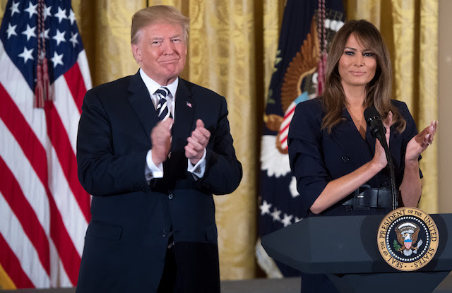 US President Donald Trump stands alongside First Lady Melania Trump (R) during an event in honor of Military Mothers and Spouses in the East Room of the White House in Washington, DC, May 9, 2018. (Photo credit: SAUL LOEB/AFP/Getty Images)