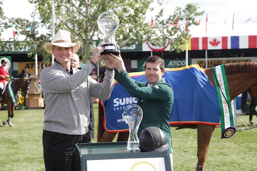 Conor Swail raises his trophy with Mark Little, Executive Vice President, Upstream, Suncor Energy.