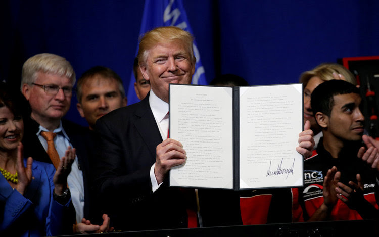 Trump smiles after signing an executive order. (Reuters/Kevin Lamarque)