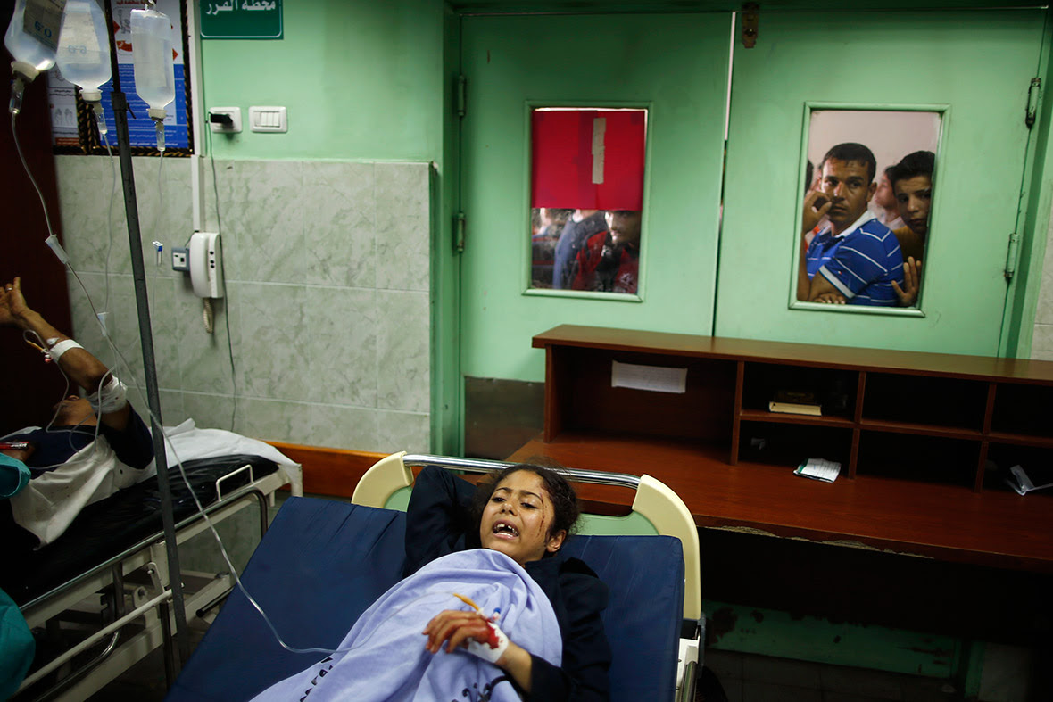 Worried Palestinians wait outside a hospital ward where a wounded girl is being treated