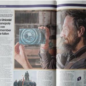 A photograph of a newspaper spread featuring a large image of a maker holding a glass work.