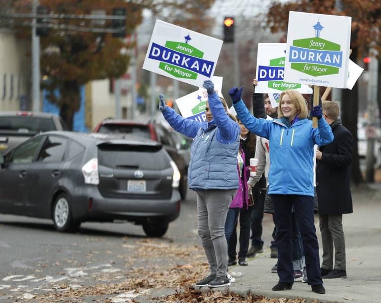 Seattle Mayor-elect Jenny Durkan, right, joins supporters waving signs on Tuesday. (Ted S. Warren/Associated Press)