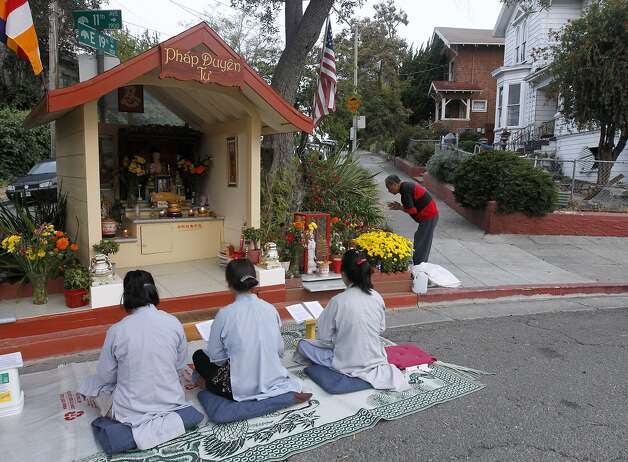 Vina Vo (left), Lien Huynh and Kieu Do pray at Buddhist shrine. Crime in the neighborhood has plunged since the shrine went up. Photo: Paul Chinn, The Chronicle