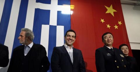 El primer ministro griego Alexis Tsipras sonríe delante de una bandera griega y una china, antes de su discurso en el buque 'Changbaishan', en el ateniense puerto de El Pireo. REUTERS / Alkis Konstantinidis