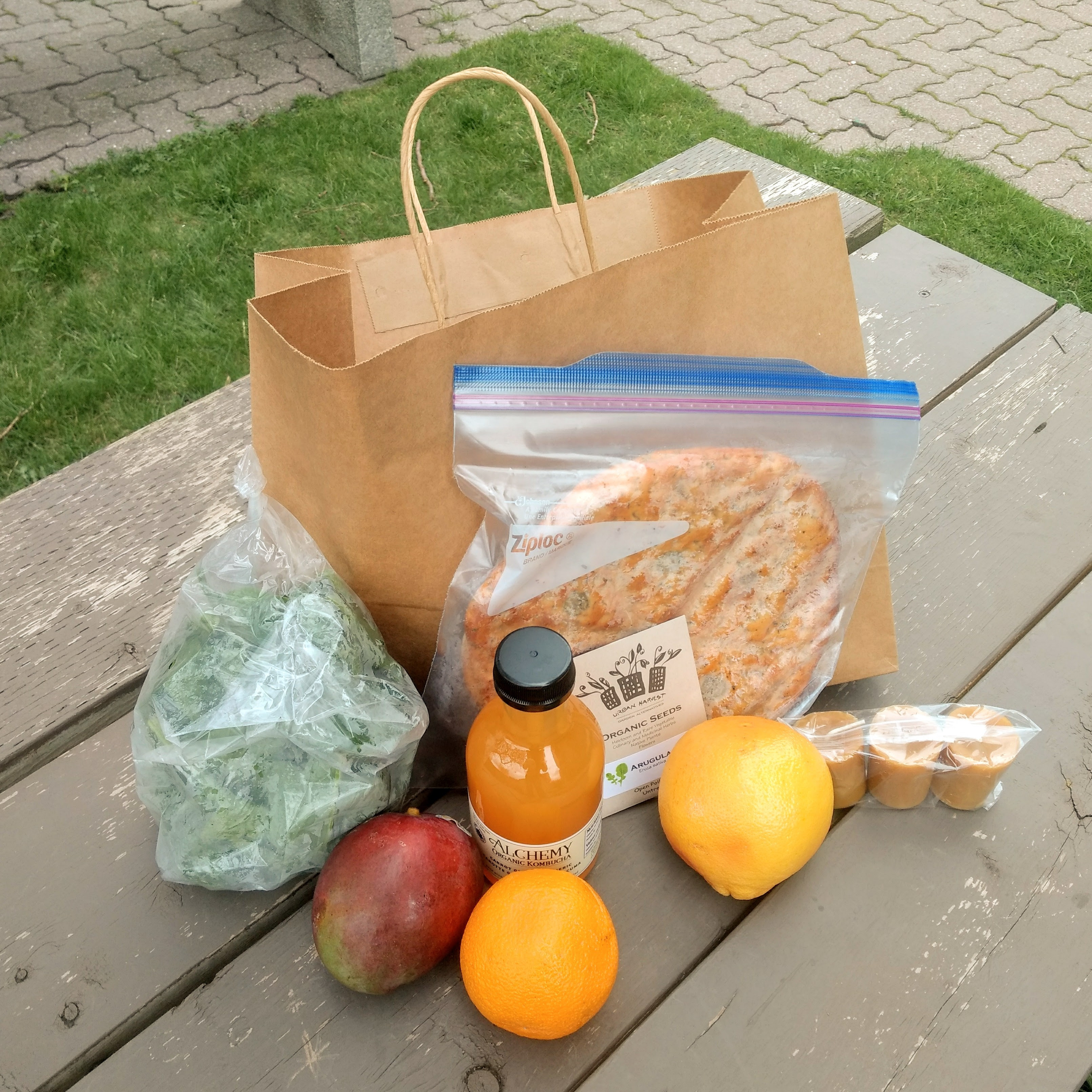A bag on a picnic table surrounded by fruit, green, kombucha, seeds, bread, and beeswax candles