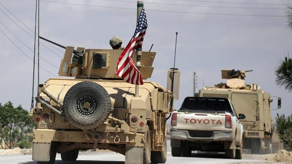 A U.S. flag flutters on a military vehicle in Manbej.