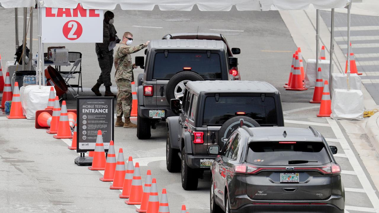 A member of the Florida National Guard directs vehicles at a COVID-19 testing site at the Miami Beach Convention Center during the coronavirus outbreak, Sunday, July 12, 2020, in Miami Beach, Floria.