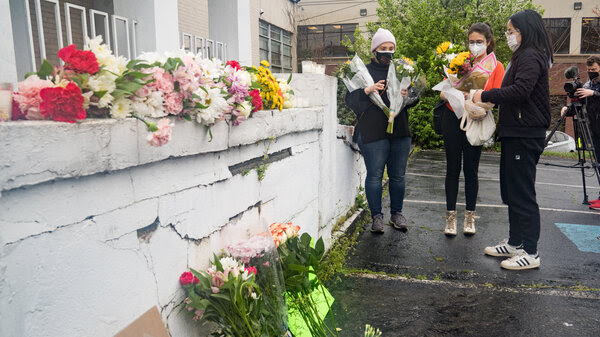 Mourners visit and leave flowers on Wednesday at the site of two shootings at spas across the street from one another in Atlanta.