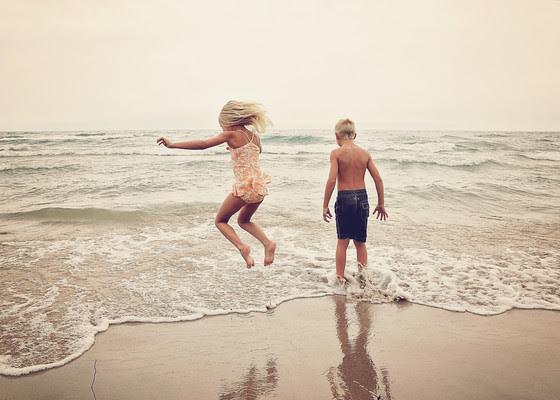 a little boy and a little girl playing on a sandy beach