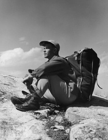 vintage hiker climber sitting on rock with pack