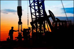 The figure above is a photograph showing oil workers at a derrick at dusk.