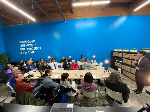 Attendees sit at 2 tables in the Volunteer Center, training to become phonebanking hosts.