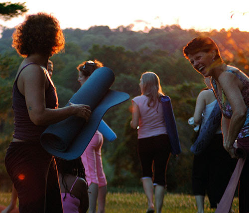 Two women rolling up yoga mats after taking a class at Morris Arboretum