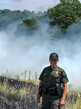 Michigan Conservation Officer Angela Greenway is pictured at the scene of a wildland fire.